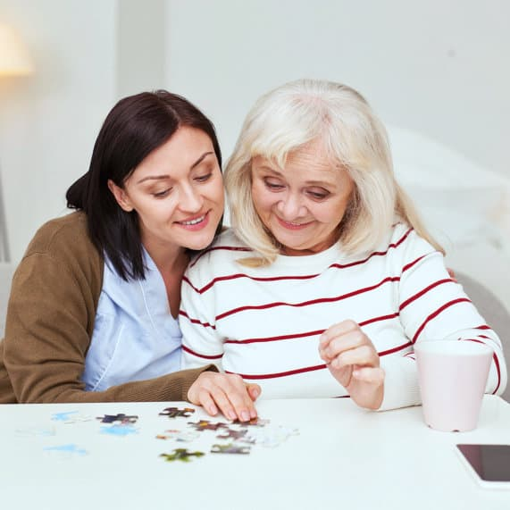 caregiver and elder patient solving puzzle