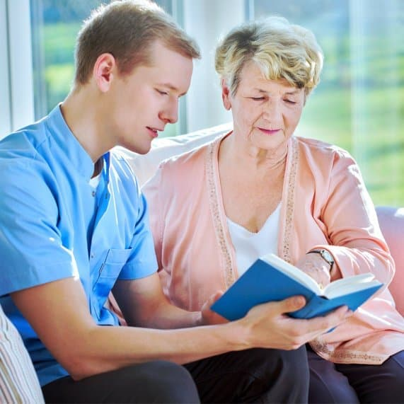 caregiver reading a book to his patient