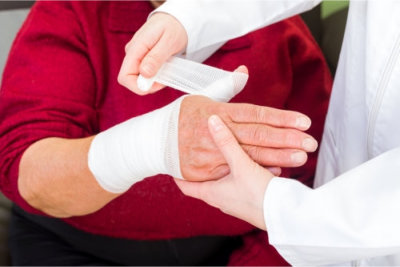 doctor bandaging the elderly woman's hand